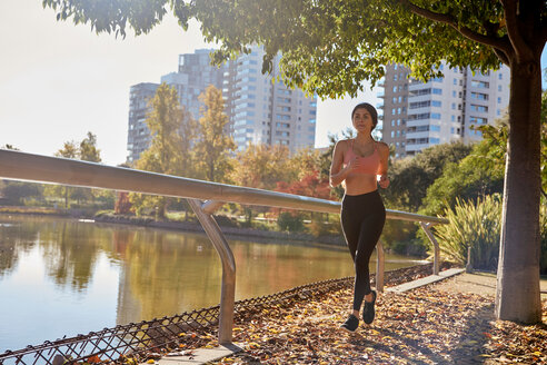 Woman jogging in city park, Barcelona, Catalonia, Spain - ISF20898