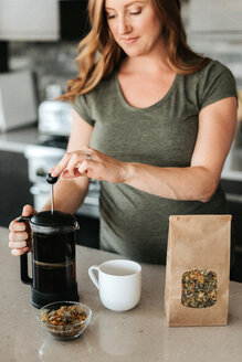 Pregnant woman brewing herbal tea with french press - ISF20907