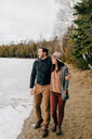 Couple walking along edge of snow field, Tobermory, Canada - ISF20937