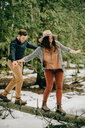 Couple balancing on fallen tree trunk in forest, Tobermory, Canada - ISF20946