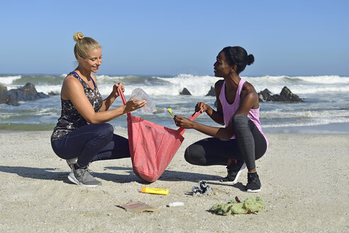 Two women cleaning the beach from plastic waste - ECPF00430