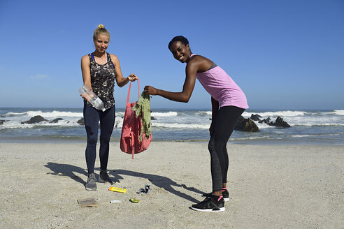 Portrait of two smiling women cleaning the beach from plastic waste - ECPF00433