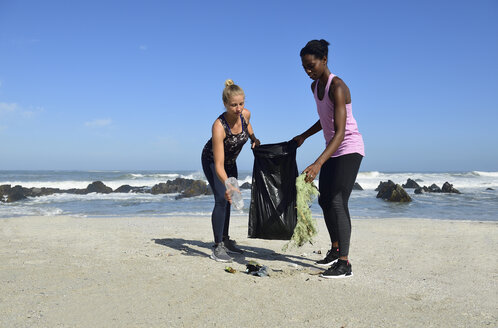 Two women cleaning the beach from plastic waste - ECPF00436