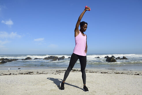 Woman doing fitness exercise with dumbbell on the beach - ECPF00445