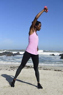 Woman doing fitness exercise with dumbbell on the beach - ECPF00448
