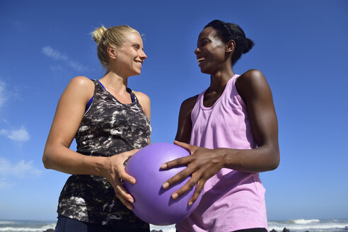 Two happy women holding fitness ball under blue sky - ECPF00451