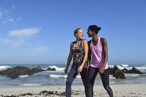 Two happy women walking on the beach - ECPF00460