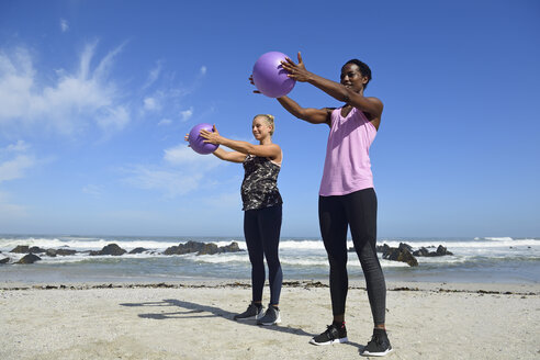 Two women doing fitness exercises with ball on the beach - ECPF00463