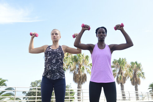 Two women doing fitness exercises with dumbbells outdoors - ECPF00466
