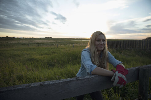 Confident young female farmer leaning on fence on farm at sunset - HEROF21056