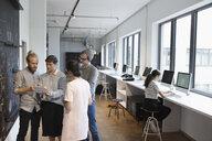 Creative business people talking, using digital tablet in office - HEROF21065