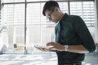 Businessman using digital tablet in office lobby - HEROF21146