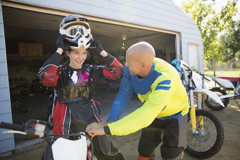 Couple putting on motorbike helmet in driveway - HEROF21167