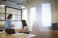 Businesswomen discussing paperwork in office meeting - HEROF21173