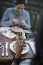 Couple with camera phones photographing food, dining at restaurant table - HEROF21206