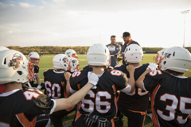 Coaches talking to teenage boy high school football team before game on sunny football field - HEROF21224