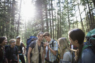 Male teacher and teenage outdoor school students exploring, hiking in woods below trees - HEROF21243
