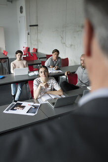 Mature students listening to professor teaching lesson in classroom - HEROF21285