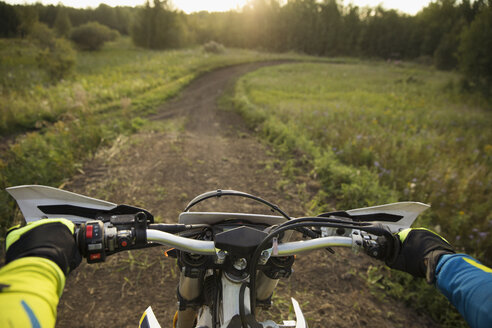 Personal perspective man riding motorbike on rural dirt road - HEROF21354