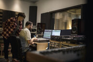 Music producers working at sound mixer in recording studio - HEROF21372