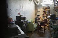 Male guitarist playing guitar at laptop in apartment - HEROF21375
