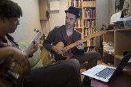 Musicians playing guitars at laptop in apartment - HEROF21378