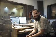 Portrait confident male music producer in recording studio - HEROF21468