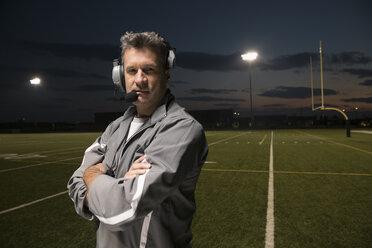 Portrait confident, tough high school football coach wearing headset on football field at night - HEROF21501