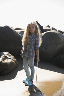 Portrait serious blonde girl with stick on sunny beach with rocks - HEROF21516