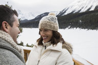 Smiling couple on deck below snowy mountains - HEROF21522