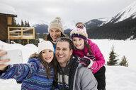 Smiling family taking selfie in snowy field - HEROF21528