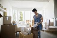 Woman packing belongings in moving boxes - HEROF21642