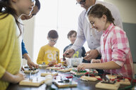 Students and teacher assembling circuit electronics at table - HEROF21654