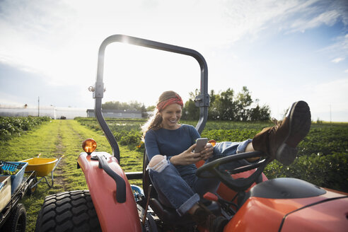 Smiling female farmer texting with cell phone on tractor on sunny farm - HEROF21711