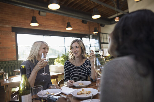 Smiling female friends drinking white wine and eating dessert, dining at restaurant table - HEROF21768