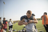 Teenage boy high school football player putting on padding for practice on sunny football field - HEROF21774