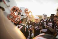 Teenage boy high school football team talking in huddle on football field - HEROF21783