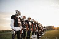 Teenage boy high school football team standing in a row on football field - HEROF21786