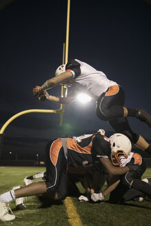 Teenage boy high school football player running back jumping over competitor to score on football field - HEROF21792