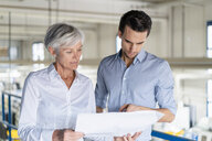 Businessman and senior businesswoman looking at plan in a factory - DIGF05730