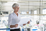 Senior woman looking at plan in a factory - DIGF05736