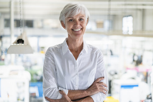 Portrait of smiling senior businesswoman in a factory - DIGF05739