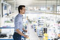Businessman on upper floor in factory overlooking shop floor - DIGF05745