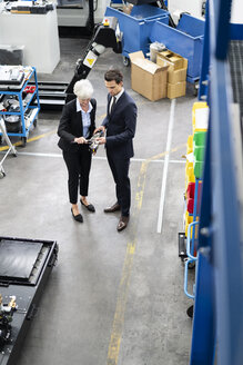 Businessman and senior businesswoman examining workpiece in a factory - DIGF05748