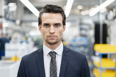 Portrait of confident businessman in a factory - DIGF05751