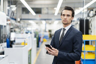 Portrait of businessman with cell phone in a factory - DIGF05754