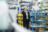 Senior businesswoman on cell phone in a factory - DIGF05763
