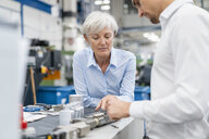 Businessman and senior businesswoman examining workpiece in a factory - DIGF05766
