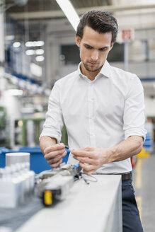 Businessman examining workpiece in a factory - DIGF05769