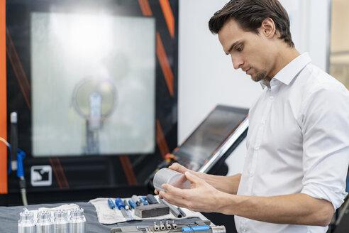Businessman examining workpiece in a factory - DIGF05772